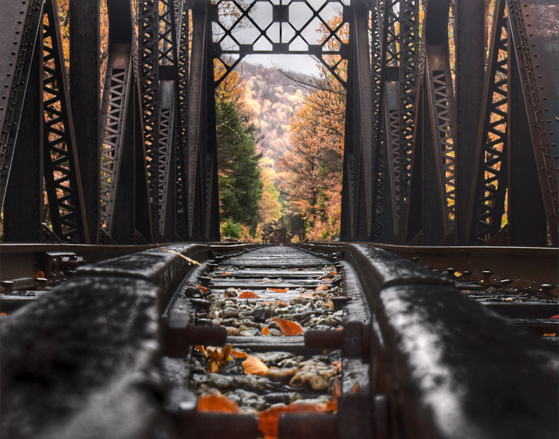 Blick auf die Gleise einer Zugbrücke in New Hampshire, die in eine waldige Landschaft in Herbstfarben hineinführt │ Zugfahrt zur Hart's Location in New Hampshire │ Tipps und Tricks für Zugfahrten │ Standort: Hart's Location, Carroll County, New Hampshire, USA, Nordamerika, Amerika │ Abenteuer Reiseblog │ Reiseanleitung │ Alles was du über das Fahren mit dem Zug wissen musst