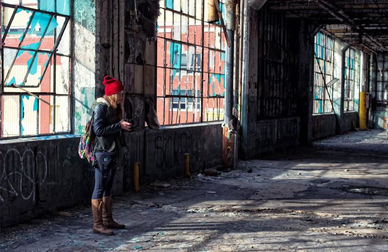 Blick auf eine hübsche junge Fotografin, die mit ihrer Kamera in einem alten leeren Gebäude steht und Bilder von der nostalgischen Ruine und von vielen coolen Graffitis macht. │ Fotografie und Videografie │ Fotos und Videos aufnehmen in Detroit in den USA │ Informationen zum Canon EF-S APS-C Kamerasystem, inklusive Kamera, Objektive, Adapter und Reiseset Empfehlungen │ Standort: Detroit, Michigan, USA, Nordamerika, Amerika │ Abenteuer Reiseblog │ Reise- und Outdoor Ausrüstung │ Canon EF-S APS-C Kamera-System und Reise-Set