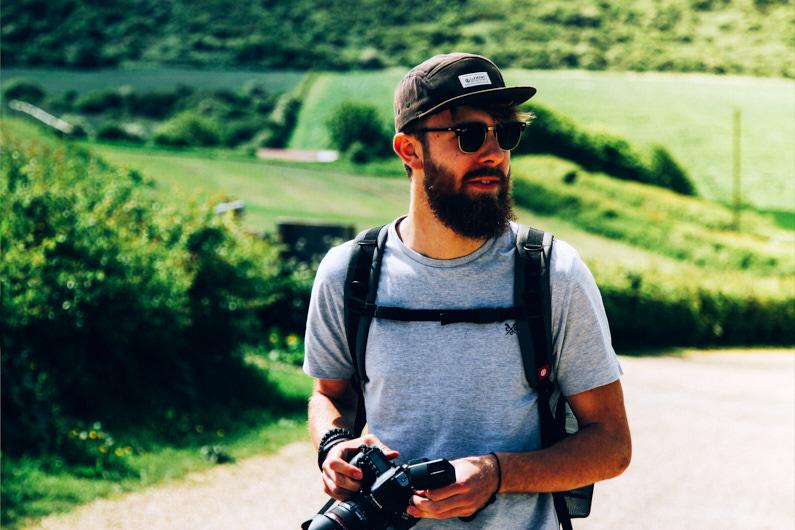 Ein hübscher junger Fotograf, bei einer Backpacking Reise durch Großbritannien, steht auf der Isle of Wight in der wunderschönen grünen Natur und macht Fotos und Videos mit seiner Canon APS-C Kamera │ Fotografie und Videografie │ Fotos und Videos aufnehmen auf der Isle of Wight in England │ Informationen zum Canon EF-S APS-C Kamerasystem, inklusive Kamera, Objektive, Adapter und Reiseset Empfehlungen │ Standort: Isle of Wight, Newport, England, Großbritannien, Europa │ Abenteuer Reiseblog │ Reise- und Outdoor Ausrüstung │ Canon EF-S APS-C Kamera-System und Reise-Set