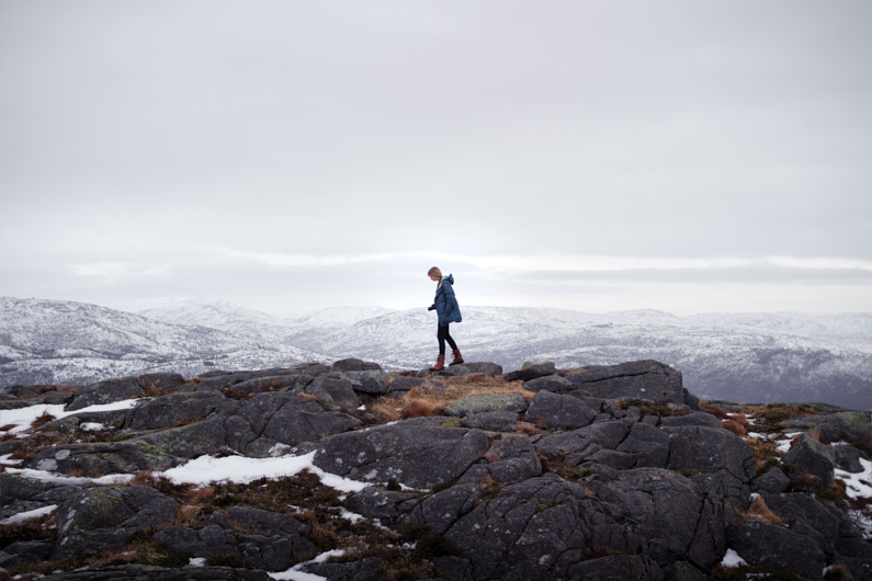 Eine hübsche junge Frau, bei einer Traumreise nach Norwegen, wandert auf dem Løvstakken Berg in Bergen und genießt die atemberaubend schöne Landschaft. Sie trägt einen warmen Daunenparka, eine lange Hose, Winterstiefel und eine Kamera um die Hals. │ Traumreise nach Bergen, Norwegen │ Die besten Daunenjacken, Daunenparkas, Daunenhosen und Daunenanzüge zum Reisen und für Outdoor Abenteuer │ Standort: Løvstakken, Bergen, Norwegen, Skandinavien, Europa │ Abenteuer Reiseblog │ Reise- und Outdoor Ausrüstung │ Daunenjacken, -parkas, -hosen und -anzüge