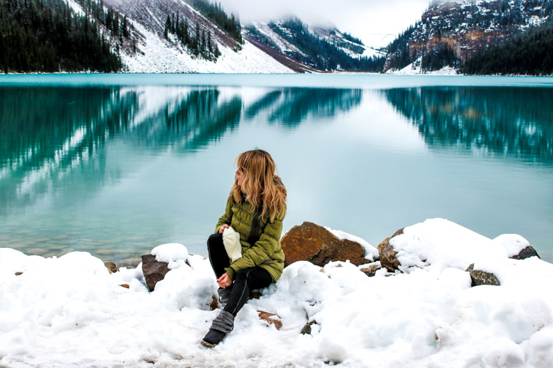 Eine hübsche junge Frau, bei einer Traumreise nach Kanada, steht an einem wundervollen See im Banff Nationalpark und genießt die wunderschöne winterliche Natur um sie herum – Bekleidet mit einem sehr warmen Daunenparka ist ihr trotz der sehr niedrigen Temperaturen schön kuschelig warm │ Traumreise in den Banff Nationalpark, Kanada │ Die besten Daunenjacken, Daunenparkas, Daunenhosen und Daunenanzüge zum Reisen und für Outdoor Abenteuer │ Standort: Banff Nationalpark, Alberta, Kanada, Nordamerika, Amerika │ Abenteuer Reiseblog │ Reise- und Outdoor Ausrüstung │ Daunenjacken, -parkas, -hosen und -anzüge