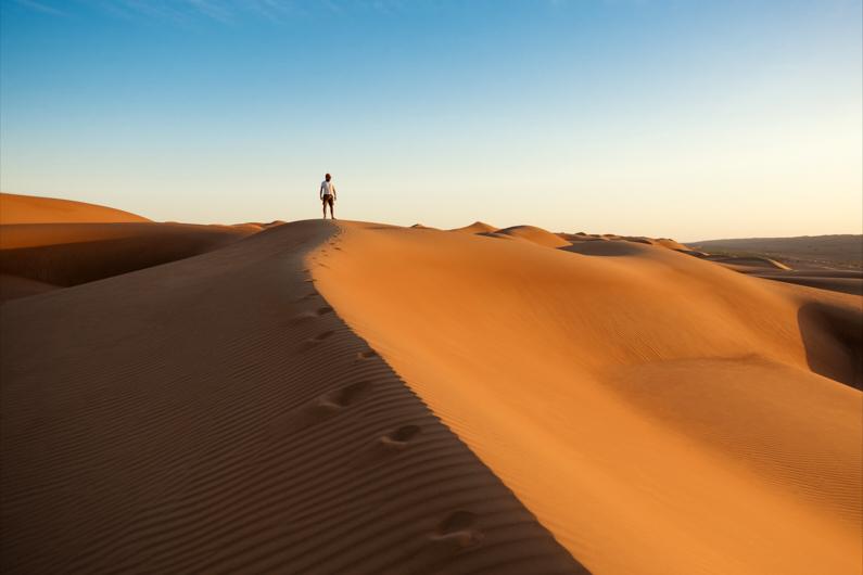 Ein Abenteurer, bei einem Ausflug in die Wüste, steht auf der Spitze einer Düne und genießt das wunderschöne Licht des Sonnenuntergangs │ Ausflug in die Wüste │ Die Entscheidung für das beste Reiseland │ Abenteuer Reiseblog │ Reiseanleitung │ Die Wahl des richtigen Reiselandes