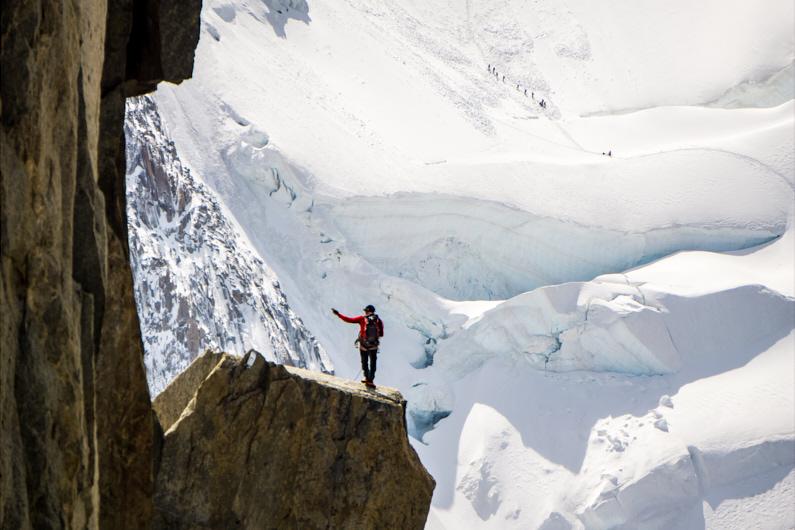 Blick auf einen Bergsteiger, der einen hohen Felsen am Aiguille du Midi bestiegen. Er schaut auf eine Gruppe von Bergsteigern in der Ferne, die dabei sind einen gewaltigen und schneeverschneiten Abhang hochzulaufen. │ Bergsteigen und Skibergsteigen am Aiguille du Midi in Chamonix │ Die perfekten Eisäxte und Eisbeile für Outdoor Abenteuer │ Standort: Aiguille du Midi, Mont-Blanc-Massiv, Chamonix, Frankreich, Europa │ Abenteuer Reiseblog │ Reise- und Outdoor Ausrüstung │ Die besten Eispickel und Eisgeräte zum Bergsteigen, Skibergsteigen, Eisklettern, Mixed-Klettern, Drytooling und für Gletscherwanderungen