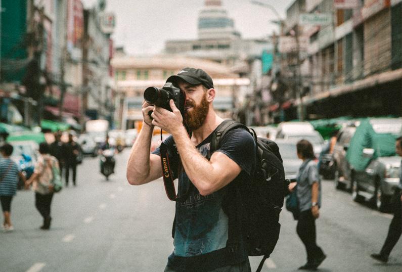 Ein hübscher Fotograf, bei einer Backpacking Reise durch Thailand, steht auf einer belebten Straße in Bangkok und macht mit seiner großen Reisekamera Urlaubsbilder und Urlaubsvideos. Er trägt einen fantastischen Lowepro ProTactic 450 AW Kamerarucksack auf den Rücken, in dem er seine gesamte Kameraausrüstung sicher verstauen kann und immer schnell und unkompliziert griffbereit hat │ Fotografie und Filmmaking │ Fotos und Videos aufnehmen in Bangkok, Thailand │ Die besten Rucksäcke für die Kameraausrüstung │ Standort: Bangkok, Thailand, Südostasien, Asien │ Abenteuer Reiseblog │ Fotografie und Filmmaking │ Die besten Kamerarucksäcke zum Fotografieren und Filmen