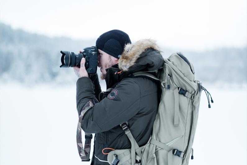 Ein Fotograf, bei einer Traumreise nach Österreich, befindet sich in der wunderschönen schneeverschneiten österreichischen Natur und nimmt mit seiner Reisekamera Fotos und Videos auf. Auf dem Rücken trägt seinen fantastischen F-stop Outdoor Kamerarucksack, in dem er seine gesamte Kameraausrüstung und Outdoor Ausrüstung sicher verstauen kann und immer schnell und unkompliziert griffbereit hat │ Fotografie und Filmmaking │ Fotos und Videos aufnehmen in Österreich, Europa │ Die besten Rucksäcke für die Kameraausrüstung │ Standort: Österreich, Europa │ Abenteuer Reiseblog │ Fotografie und Filmmaking │ Die besten Kamerarucksäcke zum Fotografieren und Filmen