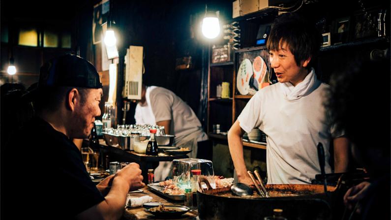 Ein Mann isst in einem einen kleinen süßen Restaurant auf Shinjuku Omoide Yokocho Straße und unterhält sich freundlich mit der Besitzerin │ Essen gehen in Shinjuku Omoide Yokocho, Shinjuku-ku │ Super Cafés, Garküchen und Restaurants finden │ Standort: Shinjuku Omoide Yokocho, Shinjuku-ku, Japan, Ostasien, Asien │ Abenteuer Reiseblog │ Reiseanleitung │ Die besten Restaurants, Garküchen und Cafés finden