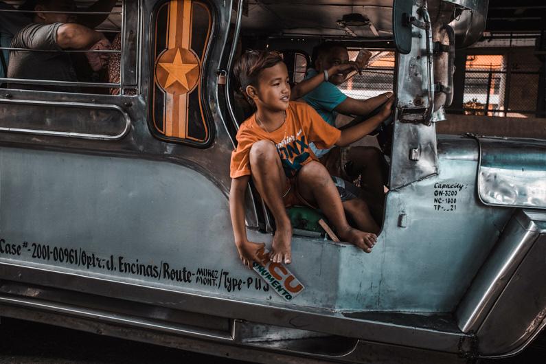 Ein kleiner Junge lehnt sich leicht auf einen fahrenden Bus und lässt sich den Fahrtwind um die Ohren wehen │ Transport in Manila auf den Philippinen │ Die günstigsten und schnellsten Transportverbindungen finden │ Standort: Manila, Philippinen, Südostasien, Asien │ Abenteuer Reiseblog │ Reiseanleitung │ Die besten Transportverbindungen von A nach B finden