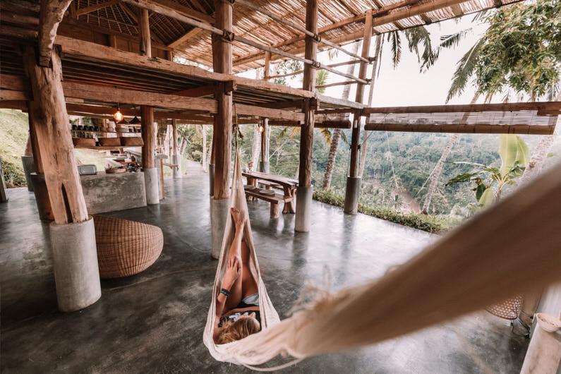 Eine hübsche junge Frau, auf einer Backpacking Reise auf Bali, liegt auf einer Hängematte in ihrer Luxus-Unterkunft und genießt eine wunderschöne Aussicht auf den Dschungel │ Backpacking in Ubud, Bali │ Die schönsten Unterkünfte finden │ Standort: Ubud, Bali, Indonesien, Südostasien, Asien │ Abenteuer Reiseblog │ Reiseanleitung │ Die besten Unterkünfte finden