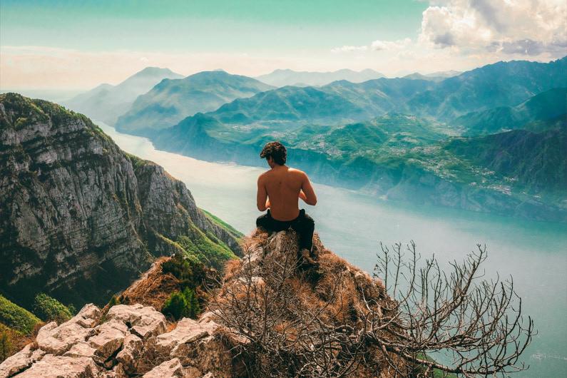 Ein junger Mann, beim Bergwandern am Monte Baldo, sitzt bei sehr sonnigen Wetter auf dem Bergsattel Bocca di Navene und genießt die atemberaube Aussicht auf die wunderschöne Berglandschaft um ihn herum und das unter ihn liegende grüne Tal mit dem Gardasee │ Bergwandern am Bocca di Navene, Monte Baldo │ Die schönsten Orte zum Reisen finden │ Standort: Bocca di Navene, Monte Baldo, Brentonico, Italien, Europa │ Abenteuer Reiseblog │ Reiseanleitung │ Die besten Urlaubsorte finden