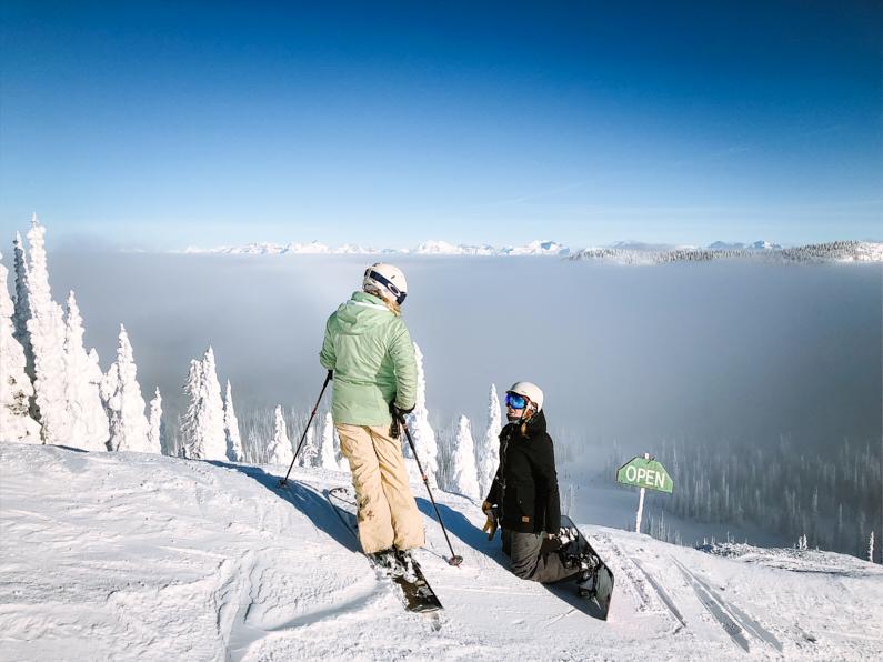 Zwei Wintersportlerinnen, eine mit Skiiern und eine mit Snowboard, befinden sich auf einen gigantischen Schnee verschneiten Berg in Montana und stehe vor einer atemberaubenden schönen Abfahrt │ Wintersport Reise nach Montana in den USA │ Kaufberatung einer Jacke zum Reisen und für Outdoor Abenteuer │ Standort: Montana, USA, Nordamerika, Amerika │ Abenteuer Reiseblog │ Reise- und Outdoor Ausrüstung │ Die perfekte Jacke