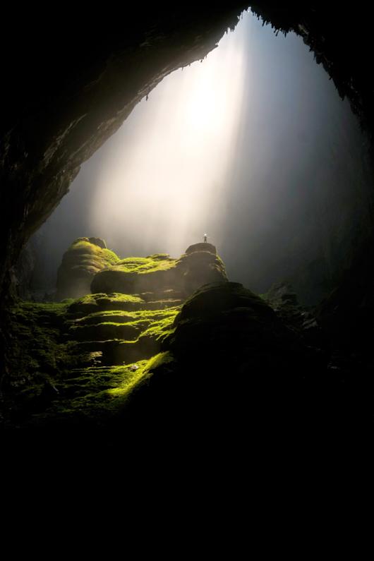 Hero Shot – Ein Mann, bei einer Wanderung im wunderschönen Phong Nha-Kẻ Bàng Nationalpark, steht mit weit ausgebreiteten Armen und seiner leuchtenden Kopflampe auf einem gigantisch großen burgähnlichen Felsen in der absolut monströsen Hang Sơn Đoòng Höhle und wird durch eine Öffnung in der Höhlendecke mit Tageslicht bestrahlt │ Wandern in der Höhle Hang Sơn Đoòng, Phong Nha-Kẻ Bàng Nationalpark │ Die besten Sehenswürdigkeiten und interessantesten Aktivitäten finden │ Standort: Hang Sơn Đoòng, Phong Nha-Kẻ Bàng Nationalpark, Quảng Bình Provinz, Vietnam, Südostasien, Asien │ Abenteuer Reiseblog │ Reiseanleitung │ Die schönsten Sehenswürdigkeiten und aufregendsten Aktivitäten finden