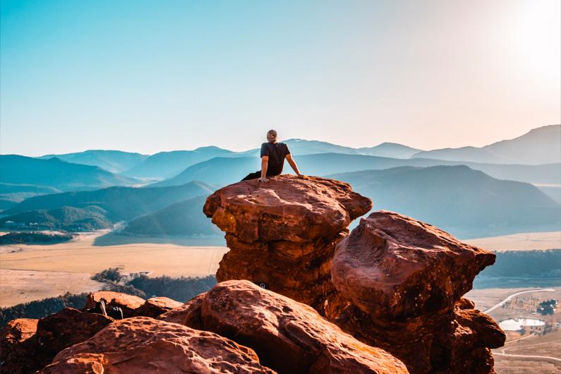 Ein junger Mann sitzt auf einen riskanten Felsenvorsprung und genießt eine atemberaubende Aussicht auf ein tief unten liegendes Tal und weit entfernte Berge │ Wandern │ Die sinnvollsten Versicherungen für Reisen │ Abenteuer Reiseblog │ Reiseanleitung │ Die wichtigsten Versicherungen auf Reisen