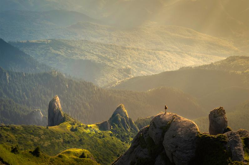 Blick auf eine junge Frau, die Backpacking durch Rumänien auf dem Berggipfel des Ciucaș Peak steht und bei super schönen Licht die atemberaubend schöne Aussicht auf das waldige Tal genießt │ Trekking zum Ciucaș Peak in den Karparten │ Die sinnvollsten Versicherungen für Reisen │ Standort: Ciucaș Peak, Karpaten, Rumänien, Europa │ Abenteuer Reiseblog │ Reiseanleitung │ Die wichtigsten Versicherungen auf Reisen