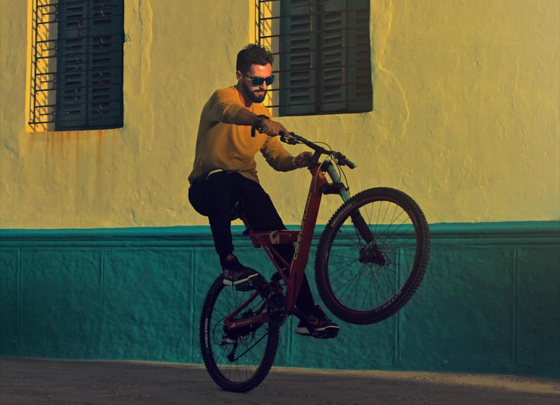 Ein sportlicher Mann, bei einer Traumreise nach Marokko, zeigt einen Trick mit einem Fahrrad und fährt nur auf einem Rad │ Traumreise nach Asilah in Marokko │ Die sinnvollsten Versicherungen für Reisen │ Standort: Asilah, Marokko, Nordafrika, Afrika │ Abenteuer Reiseblog │ Reiseanleitung │ Die wichtigsten Versicherungen auf Reisen