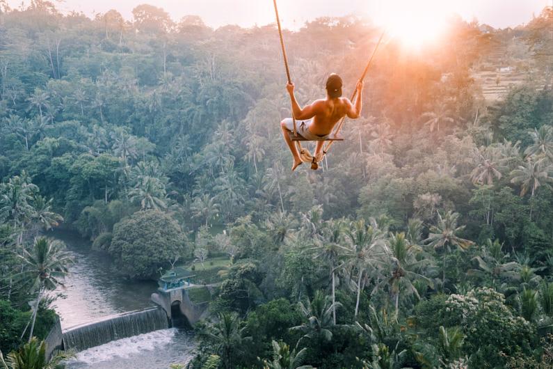 Ein junger Mann, während eines Tagesausfluges auf Bali, schwingt auf einer der gigantischen Schaukeln von Bali Swing über den tropischen Dschungel und den wunderschönen Reisterrassen │ Tagesausflug zu Bali Swing in Ubud │ Erklärung des Zwiebelschalenprinzips und Tipps wie du dich für unterschiedliche Klimazonen kleiden solltest │ Standort: Bali Swing, Abiansemal, Ubud, Bali, Indonesien, Südostasien, Asien │ Abenteuer Reiseblog │ Reise- und Outdoor Ausrüstung │ Dress in Layers! – Das Zwiebelschalenprinzip