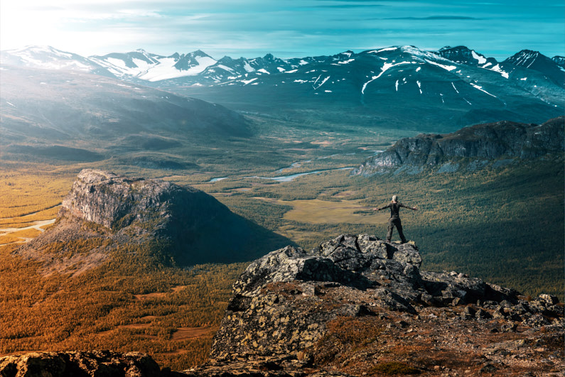 Hero Shot – Ein Mann, beim Trekking im Sarek National Park, steht mit weit ausgestreckten Armen, jubilierend auf einem Berggipfel und blickt auf ein wunderschönes grünes Tal und eine weit entfernte atemberaubende schneebedeckte Gebirgskette │ Trekking im Sarek National Park in Schweden │ Erklärung des Zwiebelschalenprinzips und Tipps wie du dich für unterschiedliche Klimazonen kleiden solltest │ Standort: Sarek National Park, Jokkmokk, Schweden, Skandinavien, Europa │ Abenteuer Reiseblog │ Reise- und Outdoor Ausrüstung │ Dress in Layers! – Das Zwiebelschalenprinzip