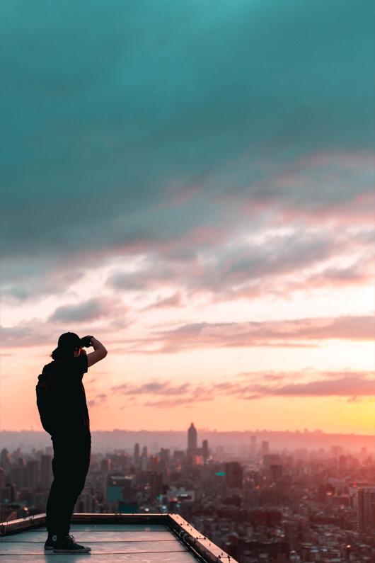 Ein hübscher junger Fotograf, bei einer Traumreise nach Taiwan, steht auf dem Dach eines Wolkenkratzers in Taipeh und macht mit seiner Fujifilm X-Mount APS-C Kamera Fotos und Videos eines fantastischen Sonnenuntergangs über der großartigen Metropole │ Fotografie und Videografie │ Fotos und Videos aufnehmen in Taipeh, Taiwan │ Informationen zum Fujifilm X-Mount APS-C Kamerasystem, inklusive Kamera, Objektive, Adapter und Reiseset Empfehlungen │ Standort: Taipeh, Taiwan, Ostasien, Asien │ Abenteuer Reiseblog │ Reise- und Outdoor Ausrüstung │ Fujifilm X-Mount APS-C Kamera-System und Reise-Set