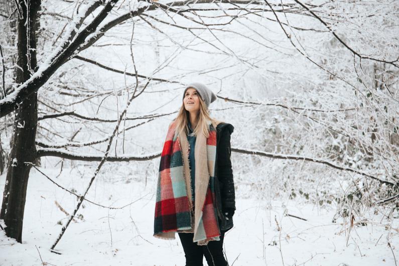 Eine hübsche junge Frau, bei einer Traumreise nach Rumänien, steht in einen tief verschneiten Wald in Pădurea Neagră und genießt die wundervolle Winterlandschaft. Sie trägt warme Handschuhe, einen schicken Schal, eine hübsche Mütze und einen Mantel mit Kapuze. │ Wandern in Pădurea Neagră, Rumänien │ Die besten Handschuhe zum Reisen und für Outdoor Abenteuer │ Standort: Pădurea Neagră, Bihor, Rumänien, Osteuropa, Europa │ Abenteuer Reiseblog │ Reise- und Outdoor Ausrüstung │ Handschuhe