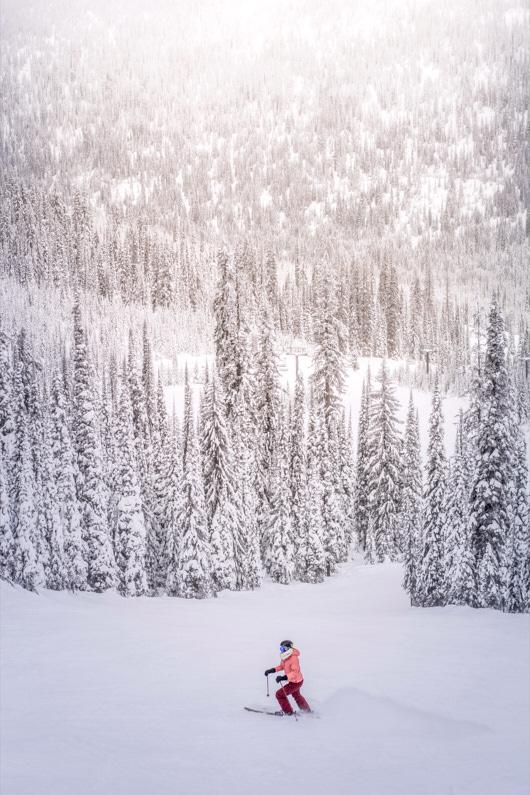 Eine Skifahrerin im Skiurlaub fährt auf einer wunderschönen Skipiste im Wald und genießt das Skifahren – Ihre super warmen Handschuhe und ihre Wintersportbekleidung helfen ihr dabei schön warm zu bleiben │ Skiurlaub │ Die besten Handschuhe zum Reisen und für Outdoor Abenteuer │ Abenteuer Reiseblog │ Reise- und Outdoor Ausrüstung │ Handschuhe