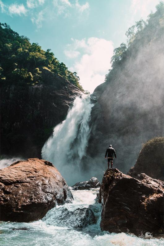 Ein Abenteurer, bei einer Backpacking Reise nach Sri Lanka, wandert an den Dunhinda Falls Wasserfällen und läuft gefährlich auf den glitschen Felsen entlang. Er trägt eine ultra kompakte wasserdichte Regenjacke, die verhindert das er klitschnass wird. │ Backpacking an den Dunhinda Falls in Sri Lanka │ Die besten Hardshelljacken und Hardshellhosen zum Reisen und für Outdoor Abenteuer │ Standort: Dunhinda Falls, Sri Lanka, Südasien, Asien │ Abenteuer Reiseblog │ Reise- und Outdoor Ausrüstung │ Hardshell Jacken und Hosen