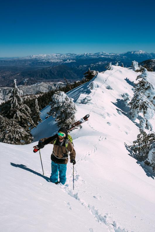 Ein Skifahrer, beim Skifahren in Kalifornien, steigt mit seinen Skiern über den Schultern den mächtigen Mount San Antonia hoch, genießt die atemberaubende Aussicht in den Bergen und freut sich schon auf eine fantastische Tiefschneeabfahrt durch die Wälder – Seine wasserdichte, robuste, atmungsaktive Hardshelljacke und Hardshellhose schützen ihn dabei super vor den vielen Schnee │ Skifahren auf dem Mount San Antonio in Kalifornien │ Die besten Hardshelljacken und Hardshellhosen zum Reisen und für Outdoor Abenteuer │ Standort: Mount San Antonio, San Gabriel Mountains, Kalifornien, USA, Nordamerika, Amerika │ Abenteuer Reiseblog │ Reise- und Outdoor Ausrüstung │ Hardshell Jacken und Hosen