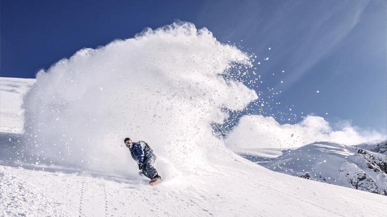 Ein Snowboarder, auf einer Snowboard-Reise, fährt im hohem Tempo eine Piste herunter und befindet sich in einer Wolke aus Schnee – Bekleidet mit einer fantastischen atmungsaktiven Hardshelljacke und Hardshellhose ist er super gut gegen Feuchtigkeit geschützt und muss sich wegen dem Schnee keine Sorgen machen │ Snowboard Reise │ Die besten Hardshelljacken und Hardshellhosen zum Reisen und für Outdoor Abenteuer │ Abenteuer Reiseblog │ Reise- und Outdoor Ausrüstung │ Hardshell Jacken und Hosen