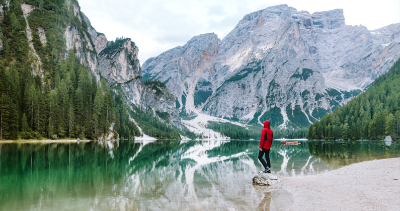 Ein Wanderer, beim Backpacking in den Pragser Dolomiten, steht am wunderschönen Pragser Wildsee und genießt eine Traumhaft en blick auf den grünen See und die herumliegenden Berge. Zum Wandern trägt er eine wasserdichte und atmungsaktive Hardshelljacke. │ Wandern am Pragser Wildsee in den Pragser Dolomiten │ Die besten Hardshelljacken und Hardshellhosen zum Reisen und für Outdoor Abenteuer │ Standort: Lago di Braies, Braies, Südtirol, Italien, Europa │ Abenteuer Reiseblog │ Reise- und Outdoor Ausrüstung │ Hardshell Jacken und Hosen