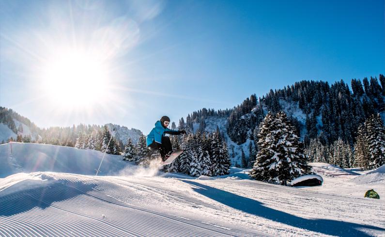 Ein Snowboarder, im Wintersport Urlaub in Portes du Soleil in der Schweiz, macht bei wunderschönen sonnigen Wetter einen sehr hohen Sprung auf der steilen Piste und geniest die fantastische waldige Berglandschaft um ihn herum – Besonders bei sonnigen Wetter ist die Wahl zwischen Hardshell und Softshell Wintersportkleidung besonders wichtig │ Skiurlaub/Wintersportreise in Portes du Soleil in der Schweiz │ Vergleich von Hardshell und Softshell Kleidung │ Standort: Portes du Soleil, Schweiz, Europa │ Abenteuer Reiseblog │ Reise- und Outdoor Ausrüstung │ Hardshell vs. Softshell Kleidung