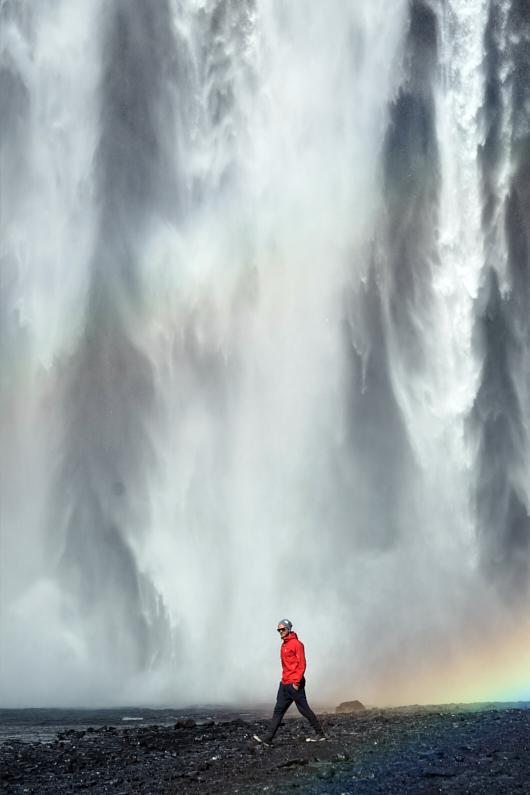 Ein junger hübscher Wanderer läuft mit seiner Hardshell oder Softshell vor dem gewaltigen Wasserfall Skógafoss in Island entlang │ Ausflug nach Skógafoss in Island │ Vergleich von Hardshell und Softshell Kleidung │ Standort: Skógafoss, Island, Skandinavien, Europa │ Abenteuer Reiseblog │ Reise- und Outdoor Ausrüstung │ Hardshell vs. Softshell Kleidung