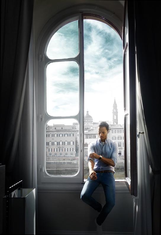 Ein hübscher junger Mann, bei einem Städtetrip in Florenz, sitzt auf einem Fensterbrett, vom dem man einen fanatischen Ausblick auf die wunderschöne italienische Stadt Florenz in der Toskana hat. Er trägt ein super stylisches Hemd und eine schöne lange Hose. │ Städtetrip nach Florenz in der Toskana │ Die besten Hemden zum Reisen und für Outdoor Abenteuer │ Standort: Florenz, Toskana, Italien, Europa │ Abenteuer Reiseblog │ Reise- und Outdoor Ausrüstung │ Hemden
