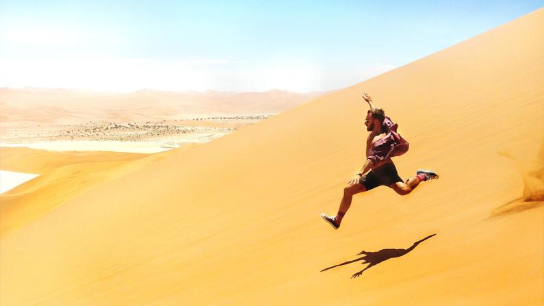 Ein Mann, bei einer Abenteuerreise nach Namibia, läuft ein der Wüste mit hohen Tempo eine steile Düne herunter. Er trägt ein offenes Hemd, eine kurze Short, Socken und Freizeitschuhe. │ Abenteuerreise in die Sossusvlei Sand Dunes in Namibia │ Die besten Hemden zum Reisen und für Outdoor Abenteuer │ Standort: Sossusvlei Sand Dunes, Namib Naukluft Park, Namibia, Südliches Afrika, Afrika │ Abenteuer Reiseblog │ Reise- und Outdoor Ausrüstung │ Hemden