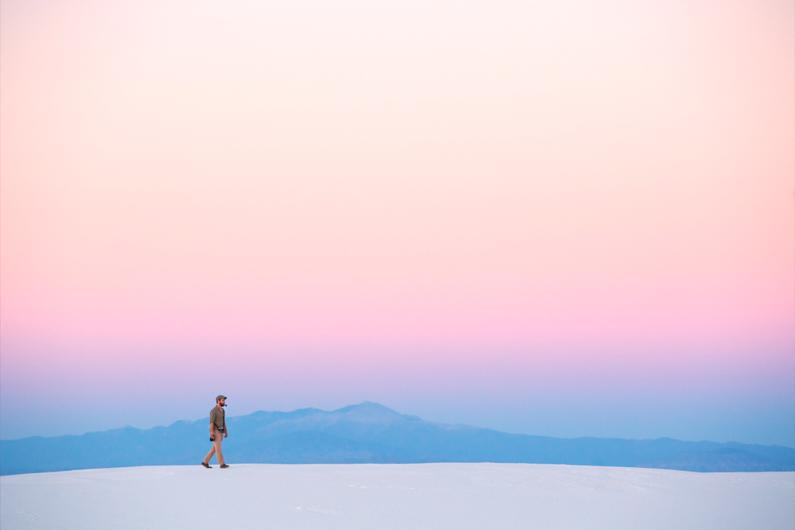 Ein hübscher junger Mann, bei einer Wanderung in der Wüste, wandert mit seiner Kamera herum und genießt einen wundervollen Sonnenuntergang – Er trägt ein grün-beiges kariertes Outdoor Hemd, eine lange beige Hose, braune Schuhe und eine Khaki Cap │ Wandern in White Sands, New Mexico │ Die besten Hemden zum Reisen und für Outdoor Abenteuer │ Standort: White Sands, New Mexico, USA, Nordamerika, Amerika │ Abenteuer Reiseblog │ Reise- und Outdoor Ausrüstung │ Hemden