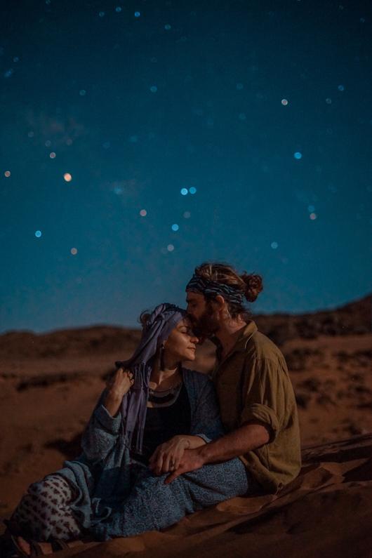 Ein Pärchen, bei einem Traumurlaub in Namibia, sitzt in den wunderschönen Sossusvlei Sanddünen, liegt sich in den Armen und genießt den atemberaubend schönen Sternenhimmel. Der Mann trägt ein luftiges Hemd, eine lockere Hose und ein Stirnband. │ Traumausflug in die Sahara Wüste Marrakech in Morokko │ Die besten Hemden zum Reisen und für Outdoor Abenteuer │ Standort: Sahara Wüste Marrakech, Morokko, Nordafrika, Afrika │ Abenteuer Reiseblog │ Reise- und Outdoor Ausrüstung │ Hemden