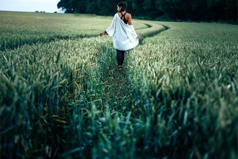 Eine hübsche junge Frau, bei einem Traumurlaub in England, wandert in Hitchin durch ein grün-gelbes Kornfeld und fährt mit ihren Händen durch das hohe Korn – Sie trägt einen langen dünnen weißen Cardigan, ein sportliches schwarzes Tank-Top, eine lange blaue Hose und schwarze Turnschuhe │ Ausflug nach Hitchin, England │ Die besten Kleider, Röcke und Cardigans zum Reisen und für Outdoor Abenteuer │ Standort: Hitchin, Hertfordshire, England, Großbritannien, Europa │ Abenteuer Reiseblog │ Reise- und Outdoor Ausrüstung │ Kleider, Röcke und Cardigans