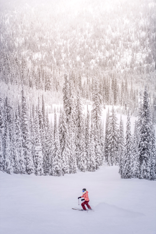 Eine Skifahrerin im Skiurlaub fährt auf einer wunderschönen Skipiste im Wald und genießt das Skifahren – Ihre super warme und atmungsaktive Wintersportbekleidung hilft ihr dabei schön warm und trocken zu bleiben │ Skiurlaub │ Detaillierter Vergleich von Baumwolle, Merinowolle und Kunstfaser, als optimaler Stoff für Kleidung zum Reisen und für Outdoor Abenteuer │ Abenteuer Reiseblog │ Reise- und Outdoor Ausrüstung │ Kleidung – Baumwolle vs. Merinowolle vs. Kunstfaser