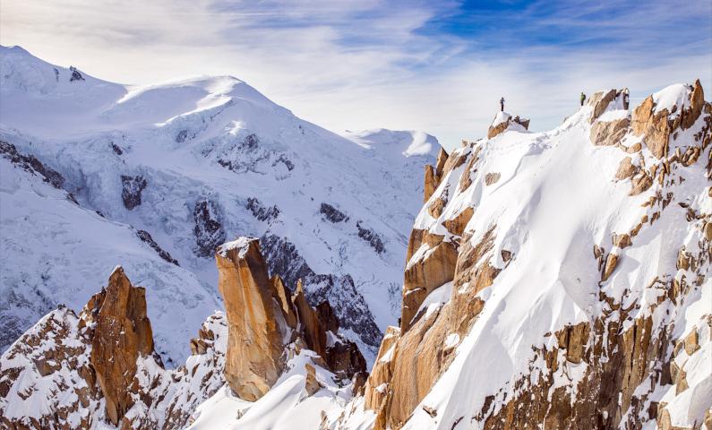 Zwei Bergsteiger, bei einer Traumreise nach Frankreich, stehen auf einer atemberaubenden steilen und zugeschneiten Bergspitze am Mont-Blanc in Chamonix – Lange Unterwäsche hilft den beiden bei kalten Temperaturen immer kuschelig warm zu bleiben │ Bergsteigen am Mont-Blanc in Chamonix │ Die beste lange Unterwäsche zum Reisen und für Outdoor Abenteuer │ Standort: Chamonix, Mont-Blanc, Frankreich, Europa │ Abenteuer Reiseblog │ Reise- und Outdoor Ausrüstung │ Lange Unterwäsche (Baselayer Leggings)