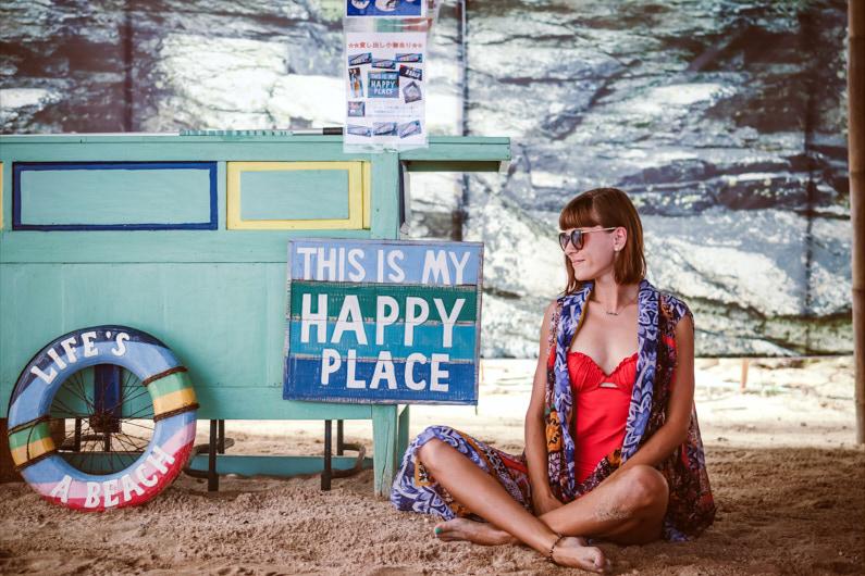 """Eine hübsche Frau sitzt entspannt am Pandawa Beach auf Bali und hat ein Schild mit der Aufschrift: """"This Is My Happy Place"""" neben sich │ Traumreise zum Pandawa Beach, Bali │ Erfülle dir deine Lebensträume │ Standort: Pandawa Beach, Bali, Indonesien, Südostasien, Asien │ Abenteuer Reiseblog │ Reiseanleitung │ Lebe deine Träume"""