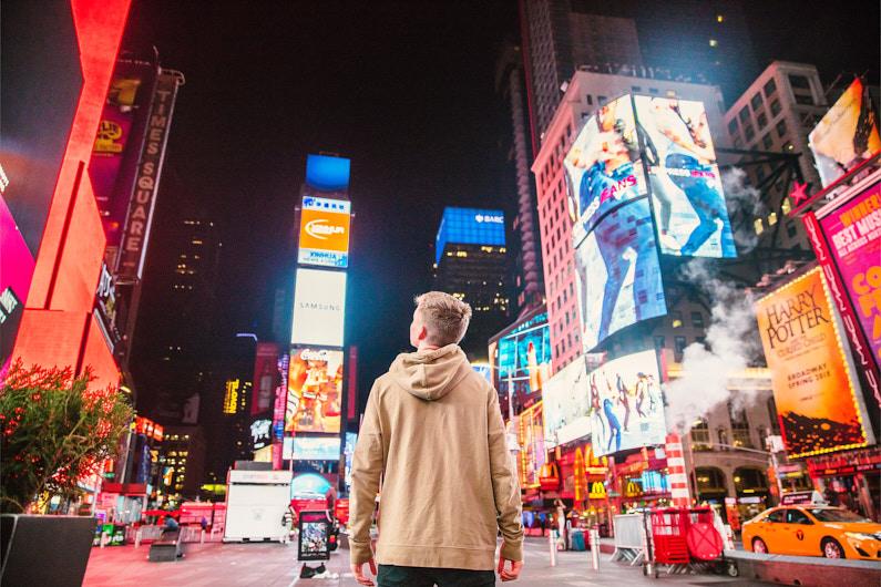 Ein hübscher junger Mann, bei einem Städtetrip in eine große Metropole, läuft eine super belebte und leuchtende Straße entlang und genießt all den Trubel und Action. Er trägt ein Long Sleeve Shirt und eine lange Hose. │ Städtetrip nach New York in den USA │ Die besten Long Sleeve Shirts (Pullover und Hoodys) zum Reisen und für Outdoor Abenteuer │ New York, USA, Nordamerika, Amerika │ Abenteuer Reiseblog │ Reise- und Outdoor Ausrüstung │ Long Sleeve Shirts (Pullover und Hoodys)