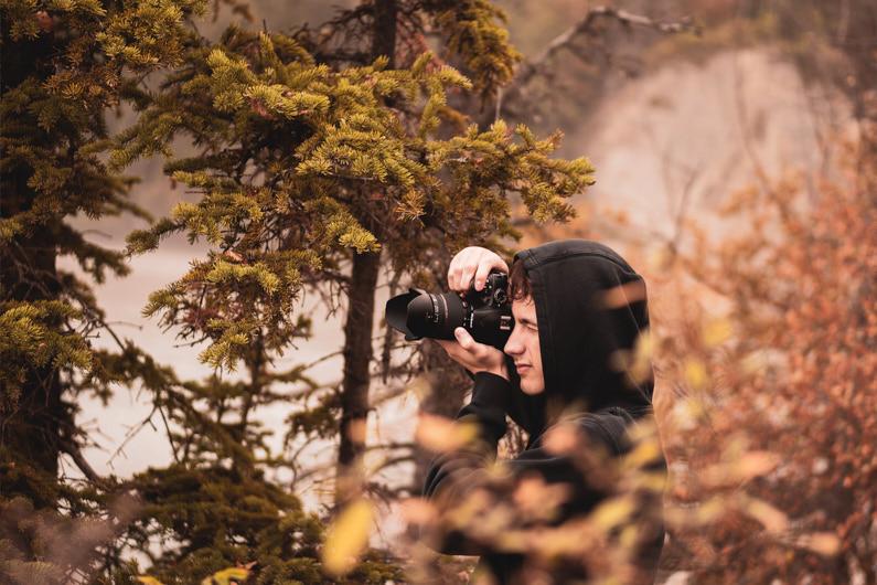 Blick auf einen jungen Fotografen, der mit seiner Nikon Kamera Fotos von den wunderschönen Herbstfarben im Wald macht. │ Fotografieren und Filmen │ Fotos und Videos aufnehmen │ Informationen zum Nikon Z-Mount Mirrorless APS-C Kamerasystem, inklusive allen Kameras, Objektiven, Adaptern und Reiseset Empfehlungen │ Abenteuer Reiseblog │ Kameraausrüstung │ Fotografie und Filmmaking │ Nikon Z-Mount Mirrorless APS-C Kamerasystem und Reisesets