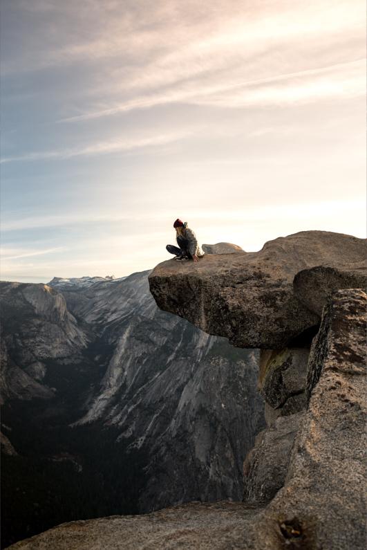Blick auf eine junge hübsche Frau, bei einer Traumreise in die USA, welche im Yosemite National Park auf den großen Felsenvorsprung am Glacier Point sitzt und auf einen gewaltigen Abgrund den Berg hinunterblickt │ Unfall, Raub oder Verlust im Urlaub │ Wandern am Glacier Point im Yosemite Nationalpark │ Wichtige Informationen für Notfälle und Schadensbegrenzung │ Standort: Glacier Point, Yosemite Valley, Yosemite-Nationalpark, Kalifornien, USA, Nordamerika, Amerika │ Abenteuer Reiseblog │ Reiseanleitung │ Notfall Informationen und Schadensbegrenzung