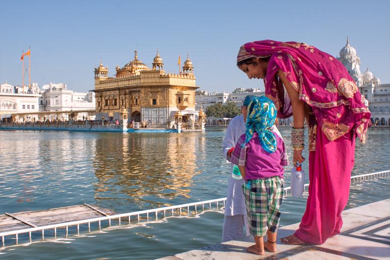 Eine Mutter steht mir ihrem Kind vor dem Goldenen Tempel von Amritsar in Indien. Beide tragen eine wunderschöne farbenfrohe Tracht │ Tagesausflug zum Goldenen Tempel vom Amritsar in Indien │ Kleidungsregeln (Dresscodes) einzelner Kulturen, Länder und auf Kreuzfahrten │ Standort: Goldener Tempel, Amritsar, Punjab, Indien, Südasien, Asien │ Abenteuer Reiseblog │ Reise- und Outdoor Ausrüstung │ Reise Kleiderknigge – Der korrekte Dresscode auf Reisen