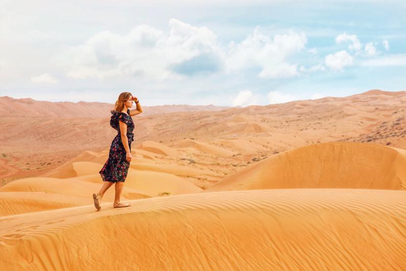 Eine hübsche junge Frau, bei einer Traumreise in den Oman, läuft auf einer sehr hohen Düne in der wunderschönen Rimal Al Wahiba Wüste und genießt ihren Urlaub aus vollen Zügen – Sie trägt ein wunderschönes blaues Sommerkleid und passende helle Sandalen dazu │ Tagesausflug in die Rimal Al Wahiba/Wahiba Sands im Oman │ Kleidungsregeln (Dresscodes) einzelner Kulturen, Länder und auf Kreuzfahrten │ Standort: Rimal Al Wahiba/Wahiba Sands, Dschanub asch-Scharqiyya, Oman, Arabische Halbinsel, Vorderasien, Asien │ Abenteuer Reiseblog │ Reise- und Outdoor Ausrüstung │ Reise Kleiderknigge – Der korrekte Dresscode auf Reisen