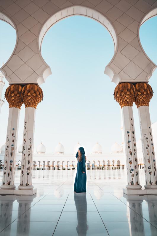 Eine hübsche junge Frau, bei einer Traumreise nach Abu Dhabi, steht in einer wundervollen islamischen Tracht in der atemberaubend schönen Scheich-Zayid-Moschee │ Ausflug zur Scheich-Zayid-Moschee in Abu Dhabi │ Kleidungsregeln (Dresscodes) einzelner Kulturen, Länder und auf Kreuzfahrten │ Standort: Scheich-Zayid-Moschee, Abu Dhabi, Vereinigte Arabische Emirate, Vorderasien, Asien │ Abenteuer Reiseblog │ Reise- und Outdoor Ausrüstung │ Reise Kleiderknigge – Der korrekte Dresscode auf Reisen