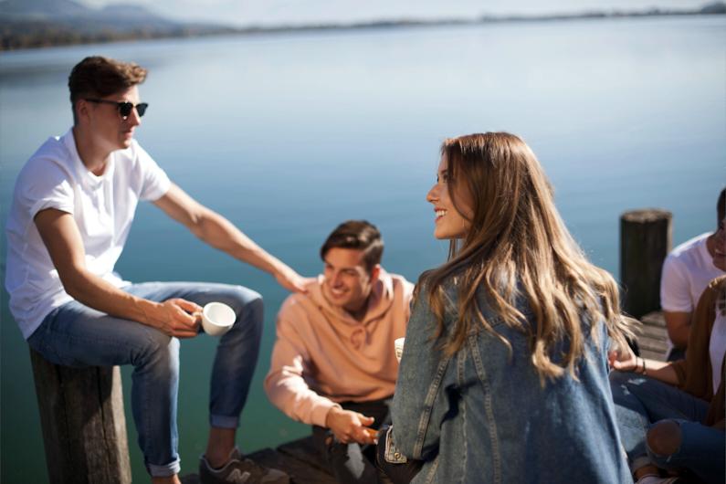 Eine Gruppe junger Menschen mit einem hübschen Mädchen im Vordergrund, bei einem Ausflug zum wunderschönen Pfäffikersee, chillt und unterhält sich auf einem Steg direkt am See und genießt das sonnige Wetter │ Ausflug zum Pfäffikersee in der Schweiz │ Alleine reisen, mit einem Reisepartner reisen, mit dem Partner reisen oder mit einer Reisegruppe reisen │ Standort: Pfäffikersee, Schweiz, Europa │ Abenteuer Reiseblog │ Reiseanleitung │ Reisebegleitung – Alleine, zu zweit oder mit einer Gruppe reisen