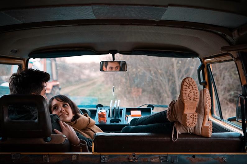 Ein junges Liebespaar bei einem Roadtrip durch Transsylvanien/Siebenbürgen – Der Junge sitzt auf den Vordersitz seines Wohnwagens und das Mädchen liegt mit Kopf auf seinen Schoß, hebt die Füße über den Nachbarsitz und schaut ihn liebevoll an │ Roadtrip durch Transsylvanien / Siebenbürgen, Rumänien │ Alleine reisen, mit einem Reisepartner reisen, mit dem Partner reisen oder mit einer Reisegruppe reisen │ Standort: Transsylvanien/Siebenbürgen, Rumänien, Europa │ Abenteuer Reiseblog │ Reiseanleitung │ Reisebegleitung – Alleine, zu zweit oder mit einer Gruppe reisen