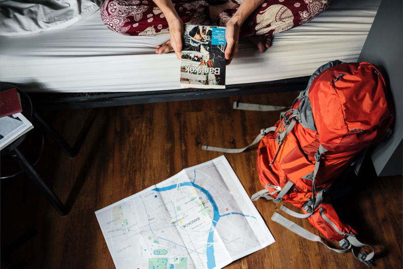 Eine junge hübsche Frau, bei einer Backpacking Reise durch Thailand, sitzt mit einem Bangkok Reiseführer auf ihrem Hostelbett und hat eine ihren handgepäckstauglichen Backpacking-Rucksack und eine Karte von Bangkok auf dem Boden liegen │ Handgepäck Backpacking Reise nach Bangkok, Thailand │ Handgepäcksreisen │ Standort: Bangkok, Thailand, Südostasien, Asien │ Abenteuer Reiseblog │ Reise- und Outdoor Ausrüstung │ Reisen mit Handgepäck