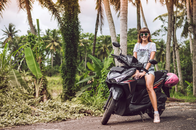 Eine junge Frau, bei einem Traumurlaub im tropischen Bali, steht mit ihrem Scooter am Straßenrad und lächelt kräftig in die Kamera │ Roadtrip/Rundfahrt durch Bali in Indonesien │ Handgepäcksreisen │ Standort: Bali, Indonesien, Südostasien, Asien │ Abenteuer Reiseblog │ Reise- und Outdoor Ausrüstung │ Reisen mit Handgepäck