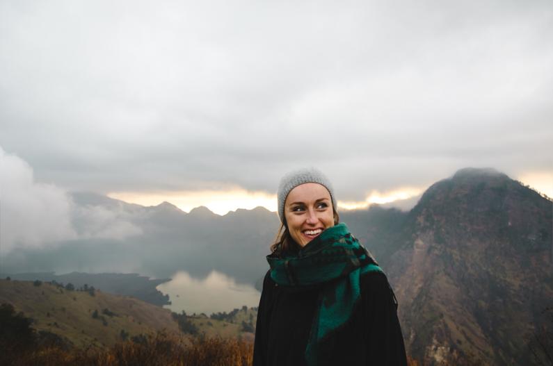 Eine hübsche junge Frau, auf einer Backpacking Reise durch Indonesien, steht nach einem mehrtägigen Trek am wunderschönen Vulkansee des 3726 Meter hohen Gunung Rinjani und genießt eine atemberaubend schöne Landschaft – Bei den niedrigen Temperaturen auf dem Vulkangipfel trägt sie eine warme Jacke sowie Mütze, Schal und Handschuhe damit ihr schön kuschelig warm bleibt │ Backpacking Reise-Trekking zum Gunung Rinjani auf Lombok │ Die besten Schals und Tücher zum Reisen und für Outdoor Abenteuer │ Standort: Gunung Rinjani, Lombok, Indonesien, Südostasien, Asien │ Abenteuer Reiseblog │ Reise- und Outdoor Ausrüstung │ Schals und Tücher