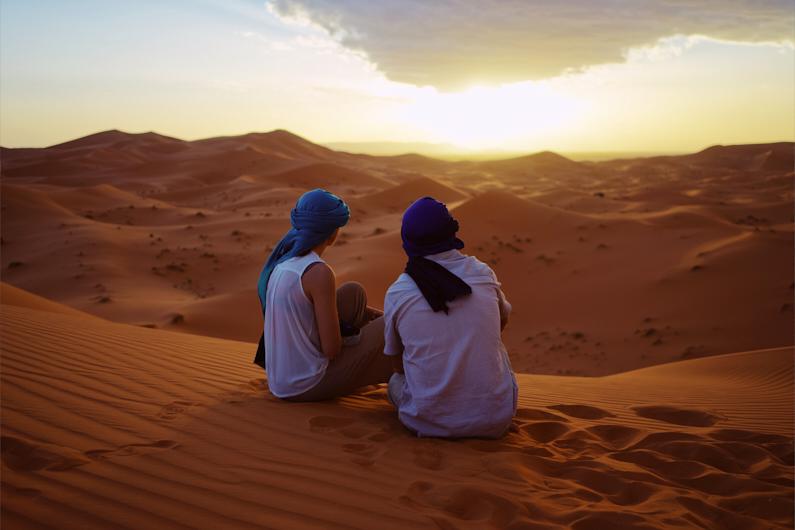 Ein Pärchen, bei einer Traumreise nach Marokko, sitzt in der Wüste von Merzouga und genießt einen wundervollen Sonnenuntergang. Beide tragen ein Berber Tuch auf den Kopf. │ Traumreise nach Merzouga, Marokko │ Die besten Schals und Tücher zum Reisen und für Outdoor Abenteuer │ Standort: Merzouga, Errachidia, Drâa-Tafilalet, Marokko, Nordafrika, Afrika │ Abenteuer Reiseblog │ Reise- und Outdoor Ausrüstung │ Schals und Tücher