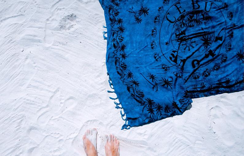 Eine hübsche junge Frau, bei einem Ausflug zum Strand, steht nach dem Schwimmen in Meer mit ihren Füßen vor ihrem super praktischen Sarong, welches sie beim ihrer Backpacking Reise als Hand- und -Standtuch nutzt │ Backpacking Reise │ Die besten Schals und Tücher zum Reisen und für Outdoor Abenteuer │ Abenteuer Reiseblog │ Reise- und Outdoor Ausrüstung │ Schals und Tücher